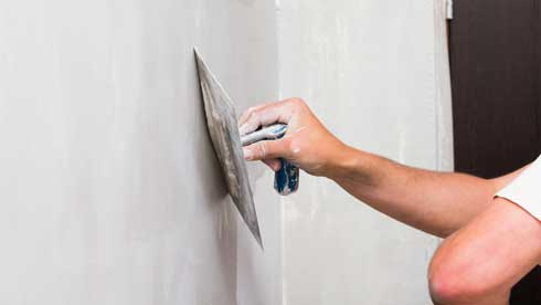 What is the Proper Method for Skim Coating a Wall or Ceiling